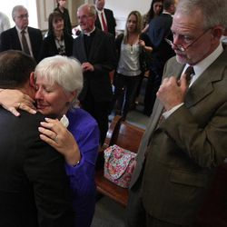 Morris County Prosecutor, Robert A. Bianchi, left, gives a hug to Judith Ann Conk, a long-time friend of Rev. Edward Hinds as her husband Richard looks on Friday April 20, 2012 in Morris County Superior Court in Morristown, N.J. Jose Feliciano , a former church janitor was sentenced Friday to life in prison without parole for the 2009 stabbing death of a beloved New Jersey priest who had fired him.
