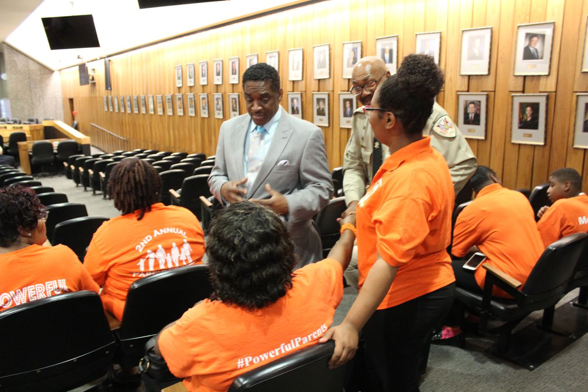 Commissioner Eddie Jones, a supporter of the extra funding, talks with Memphis LIFT parents before the meeting.