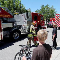 A young boy tries to help a fireman by lifting the tape for him as Unified Fire Authority firefighters fight a fire at 3381 S. 3170 East in Millcreek on Sunday, July 5, 2020.