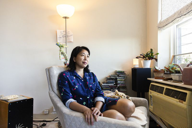 A woman sits curled in a chair in her apartment.