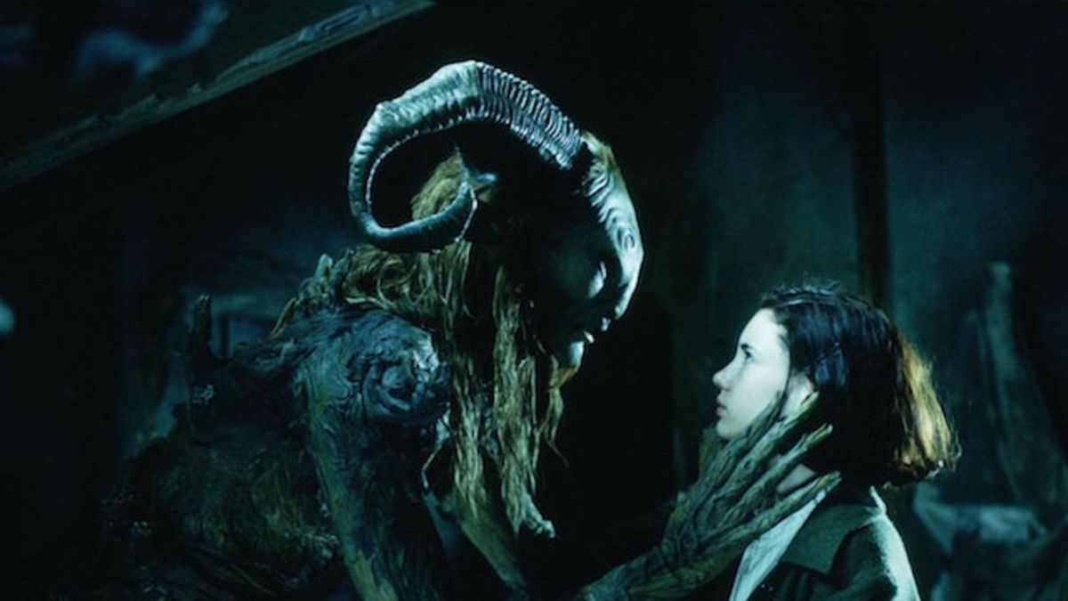 A monster with large horns and long fingers crouches down in front of a young girl.