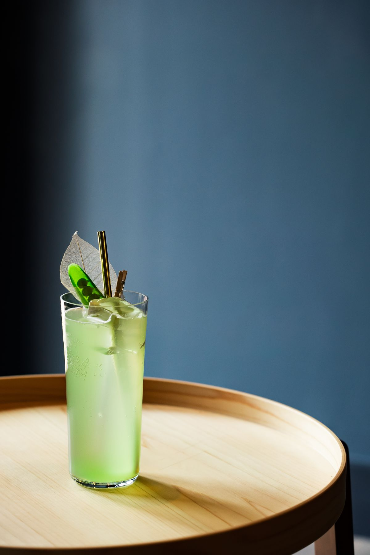 A pale green cocktail in a tall glass with a large leaf-shaped garnish and a metal straw.