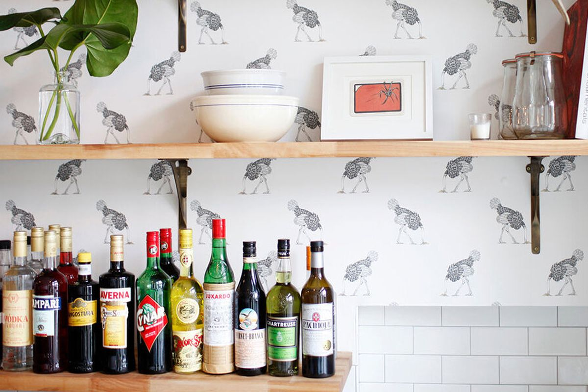 The bar at Homer, with some cookbooks lined up on a shelf, and light-colored wallpaper displaying birds