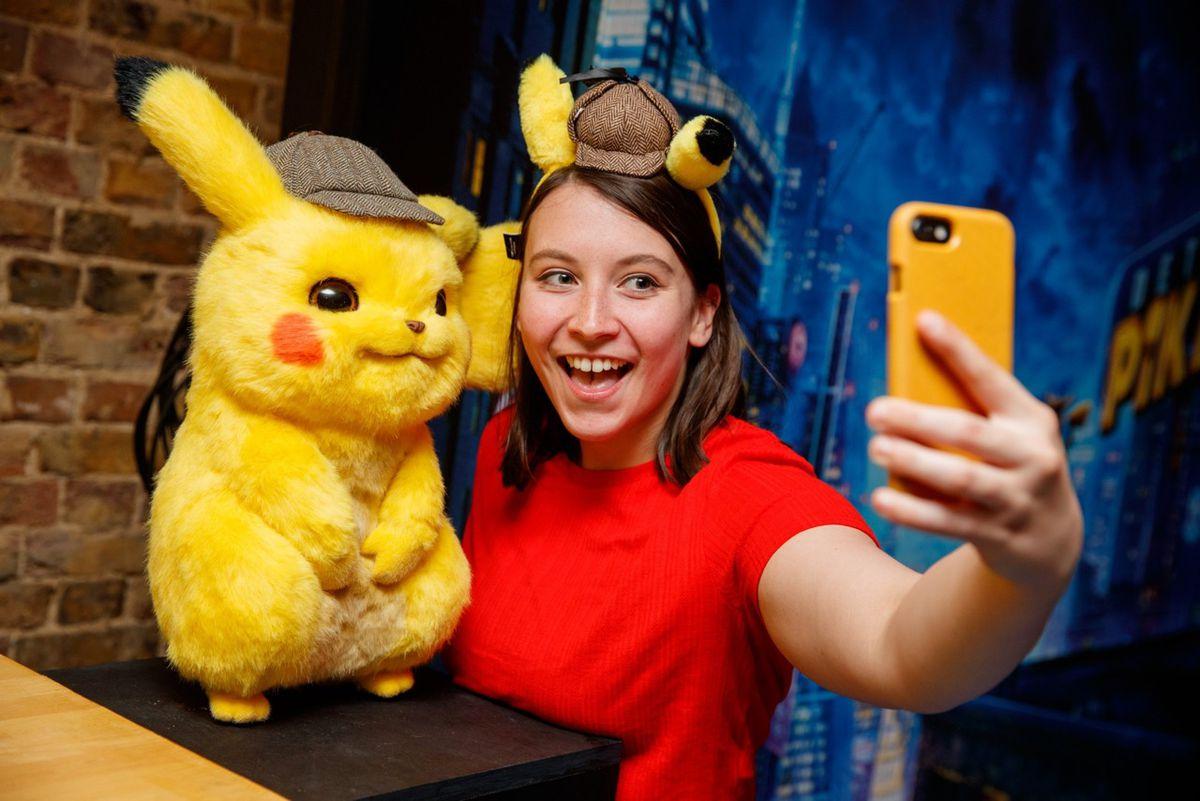 Someone posing with Pikachu at PokéBar