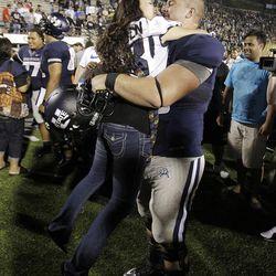 Utah State Aggies center Tyler Larsen (58) kisses his girlfriend Samantha Miller while celebrating their win over the Utah Utes  in Logan  Friday, Sept. 7, 2012.