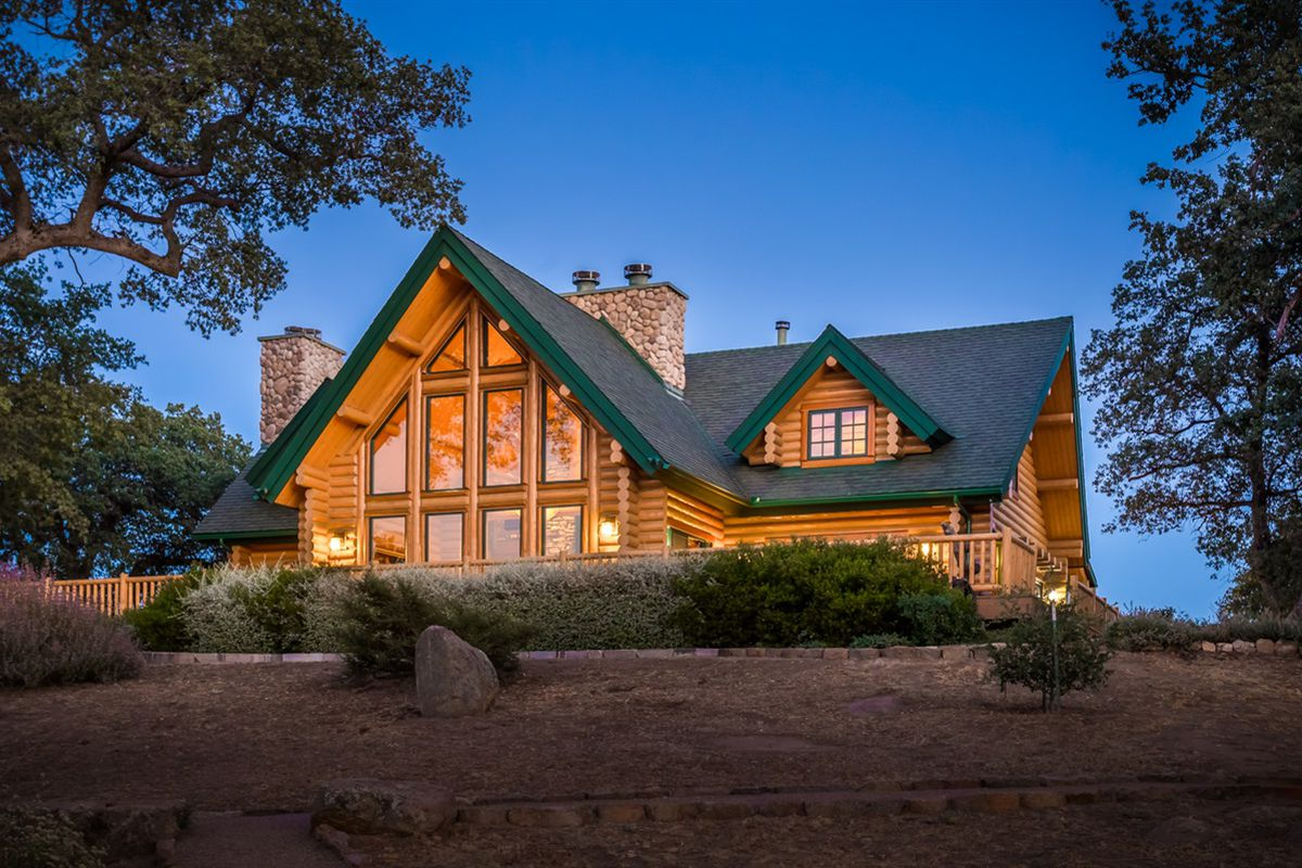 Exterior shot of large log cabin with a gable section of windows.