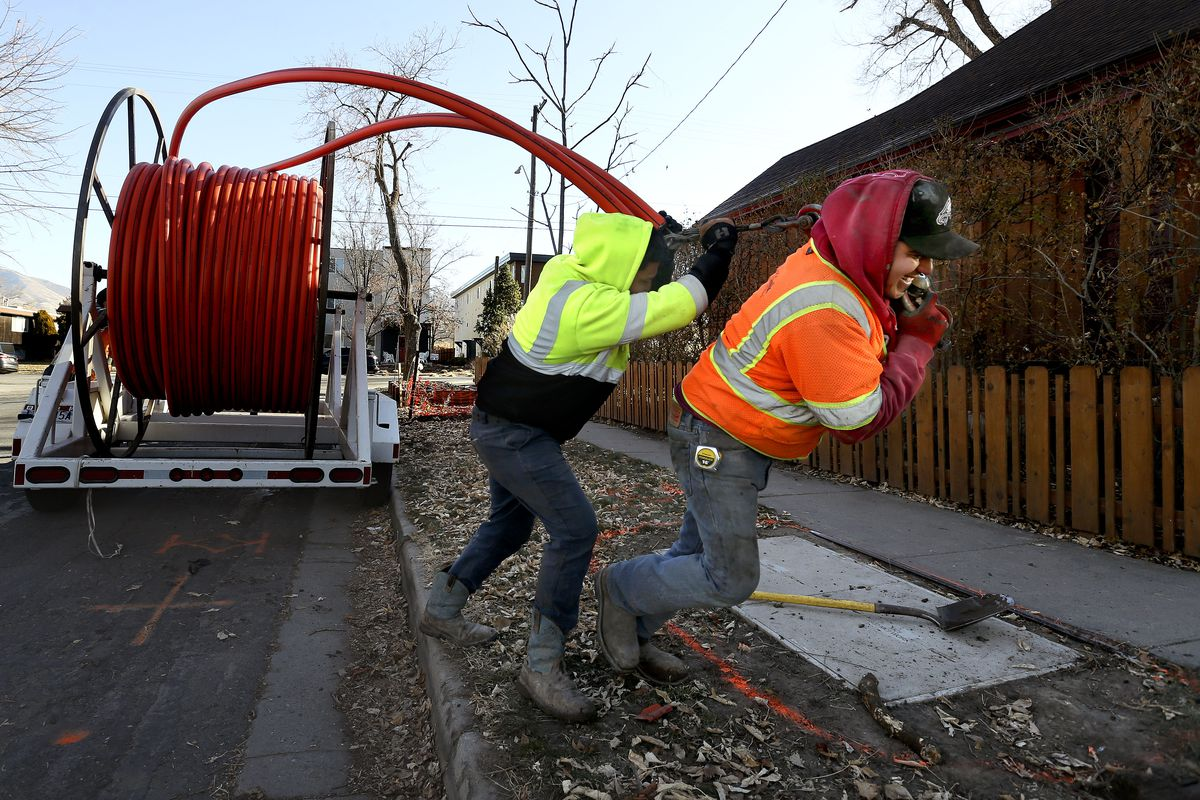 Jose Reyes, right, and Aval G., of LightLink Communications, install cable for broadband internet in Salt Lake City on Thursday, Dec. 3, 2020.