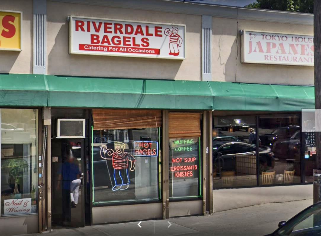 A storefront with a neon boy with a bagel in his arm muscle.