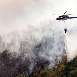 A helicopter dumps water on the Whiskey Springs Fire near Heber City  Sunday, Aug. 19, 2012.