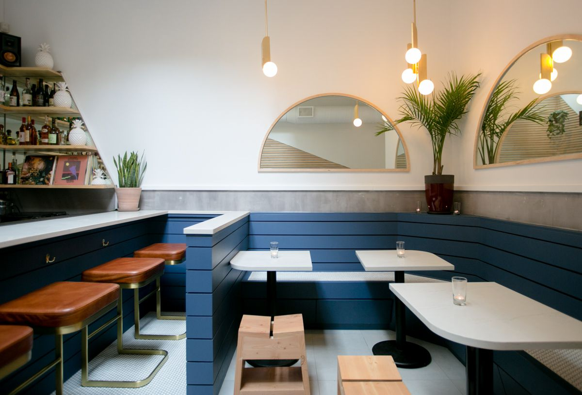 Corner seating at the Hidden Pearl with a blue wood banquette