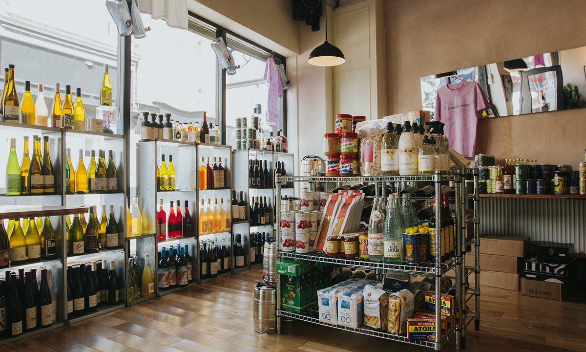 The interior of a wine shop and deli, with clear wine fridges, pink t-shirts hanging at the back, and an island with crisps, tinned fish, and jars of beans, tomatoes, and other deli goods