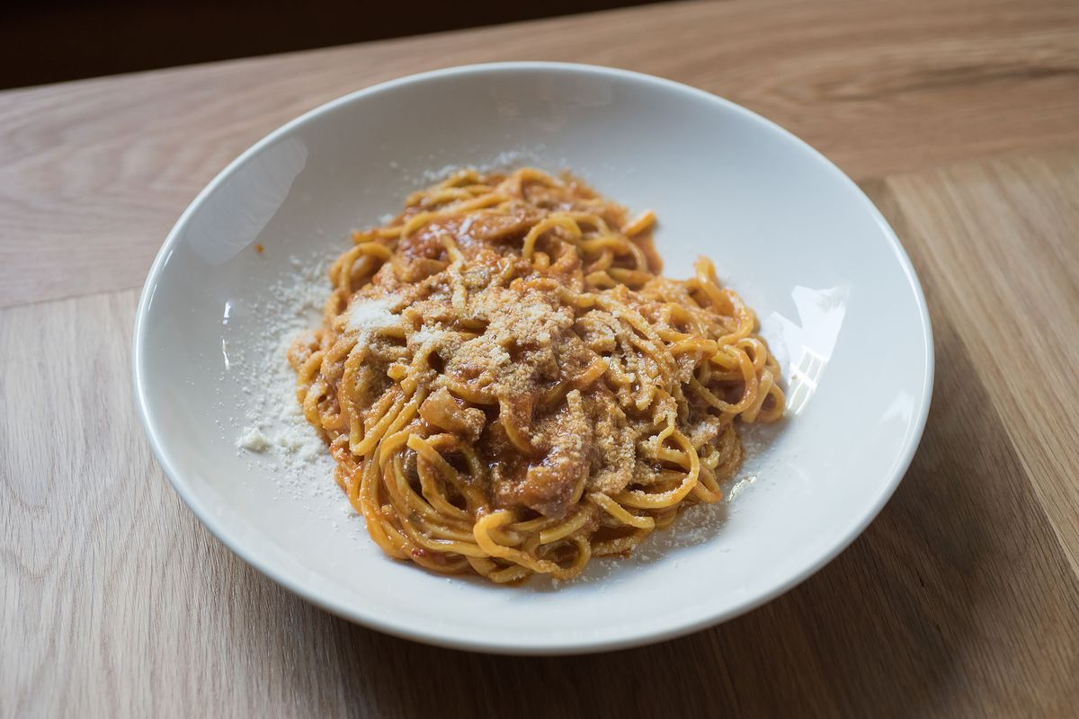 Plate of red sauce pasta on a white plate at Uovo. Tonnarelli amatriciana at Uovo.