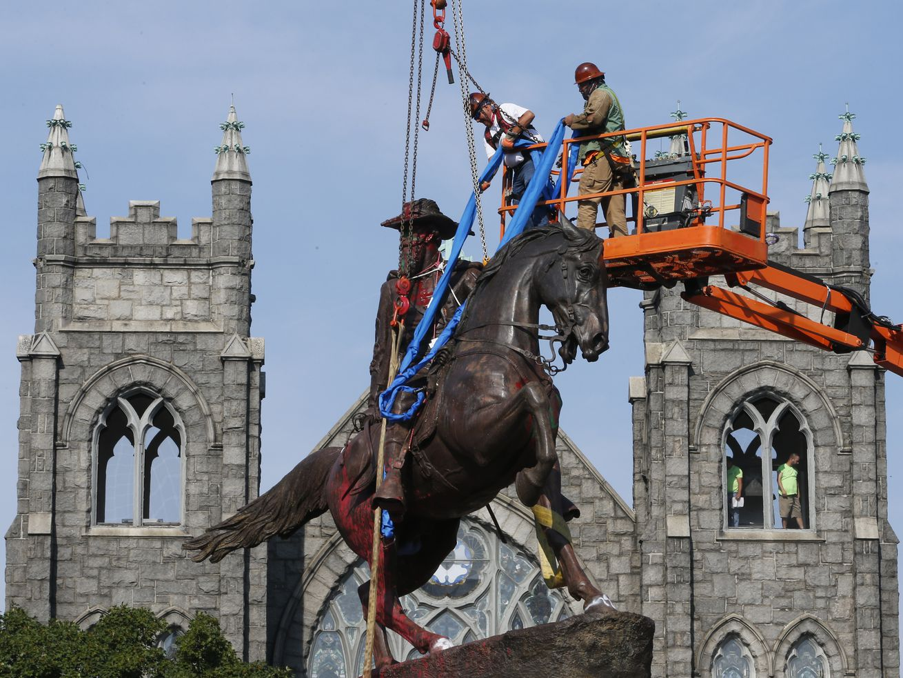In this July 7, 2020, file photo, crews attach straps to the statue Confederate General J.E.B. Stuart on Monument Avenue in Richmond, Va. At least 160 Confederate symbols were taken down or moved from public spaces in 2020.