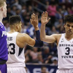 Brigham Young Cougars forward Yoeli Childs (23) and Brigham Young Cougars guard Elijah Bryant (3) high five in Provo on Thursday, Dec. 28, 2017. BYU won 69-45.