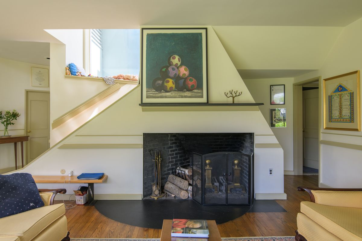 A living area with a fireplace. A work of art hangs over the mantle. There are couches and a coffee table. On a ledge by the fireplace are a row of stuffed toy animals.