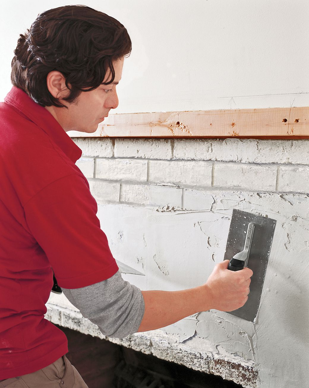 Man Tiles Over Bricks Of Fireplace With Finishing Trowel