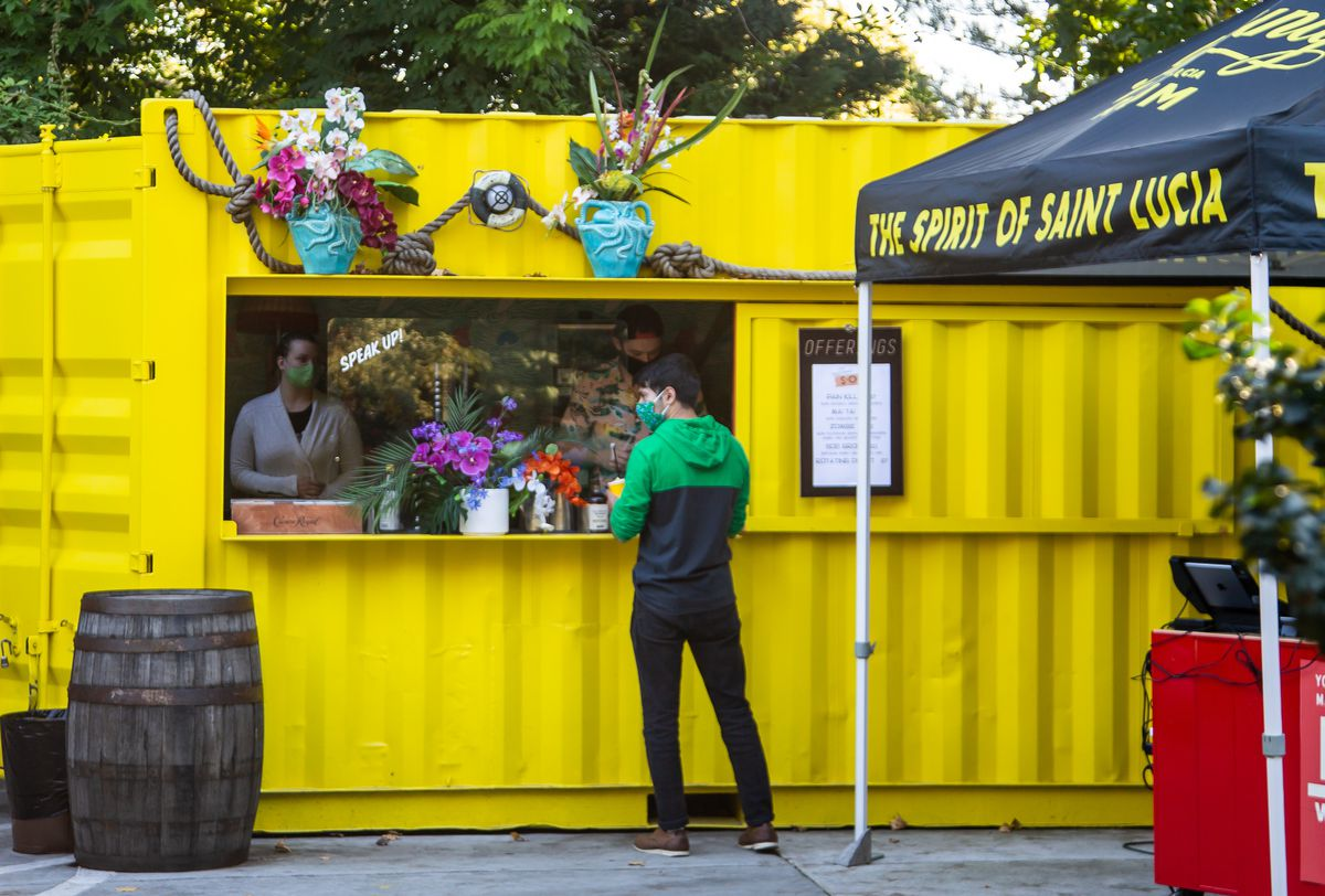 A bright yellow metal container houses Victory Sandwich Bar's outdoor tiki bar to-go window. A masked staff member stands inside the window assisting a patron in black pants, green and black hoodie, and mask
