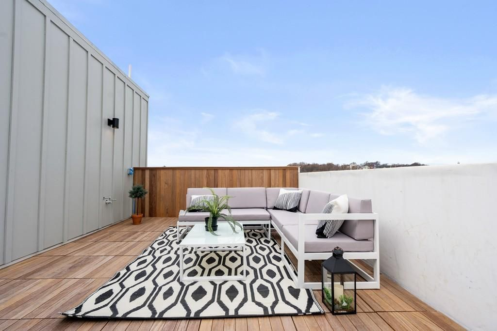 A rectangular roof deck with furniture.
