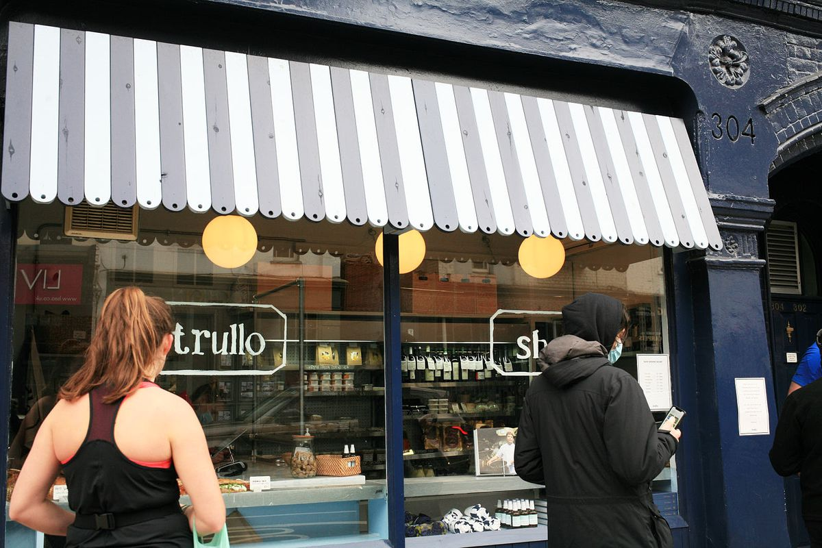 Customers queue outside Trullo, the Italian restaurant in Islington, with a striped awning overhanging the window