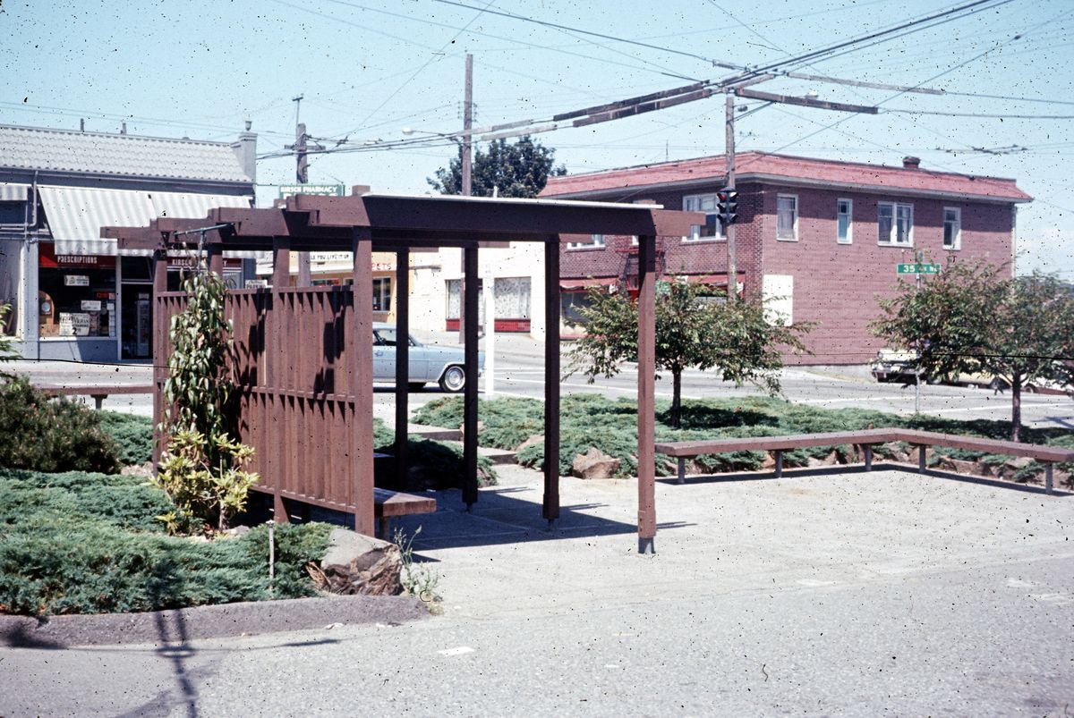 A bus stop with a wood-slat wall to the left and a trellis up top behind a paved area.