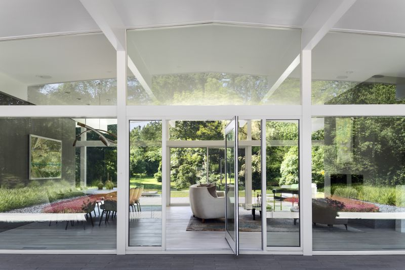 A swinging glass door opens to a living room.
