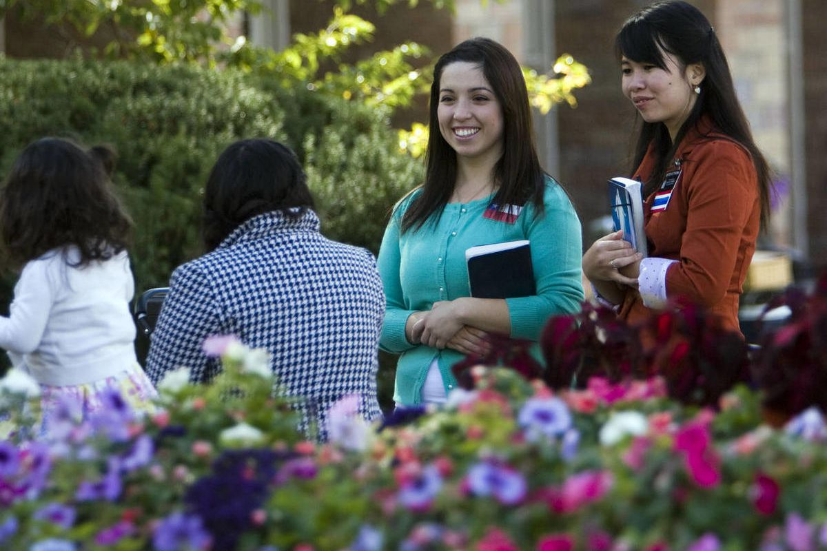 File photo of sister missionaries talking to visitors on Temple Square during the afternoon session of general conference, Sunday, Oct. 7, 2012.