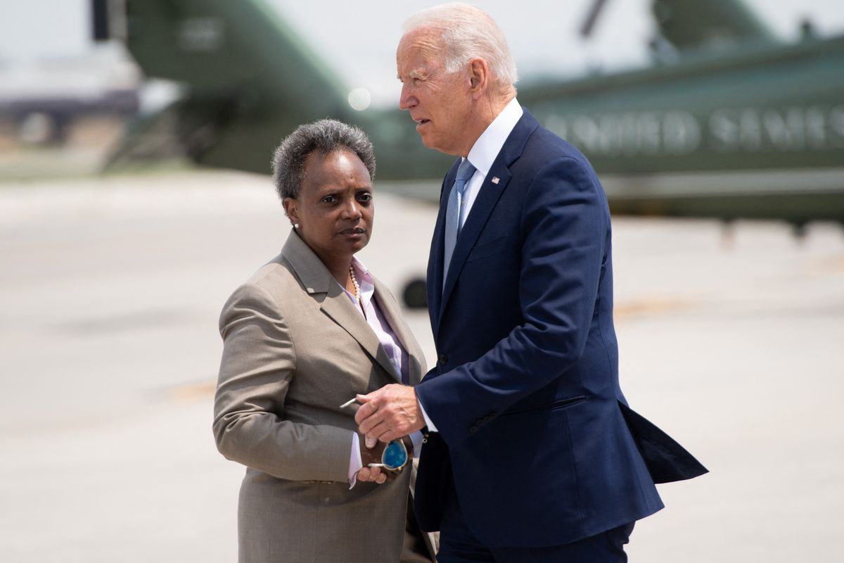 President Joe Biden greets Chicago Mayor Lori Lightfoot (left) as he disembarks from Air Force One upon arrival at O'Hare International Airport in Chicago, Illinois, on Wednesday.