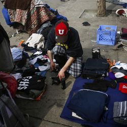 """Criss, left, folds and reorganizes clothes outside the Catholic Community Services (200 S. and 500 W.) next to the Road Home, called """"The Block,"""" in Salt Lake City on Wednesday, March 8, 2017. Chris, originally from Ohio, has been exited from the Road Home until March 12 and has relapsed since being removed from the shelter."""