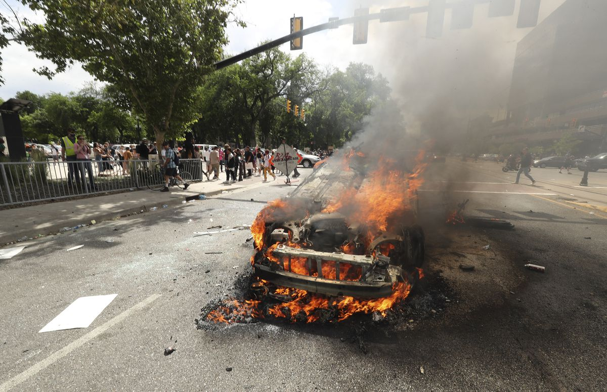 A police car is engulfed in flames as people protest police brutality in Salt Lake City on Saturday, May 30, 2020. Protesters joined others across the nation to decry the death of George Floyd, a black man, who died while being taken into custody by police in Minneapolis earlier this week.