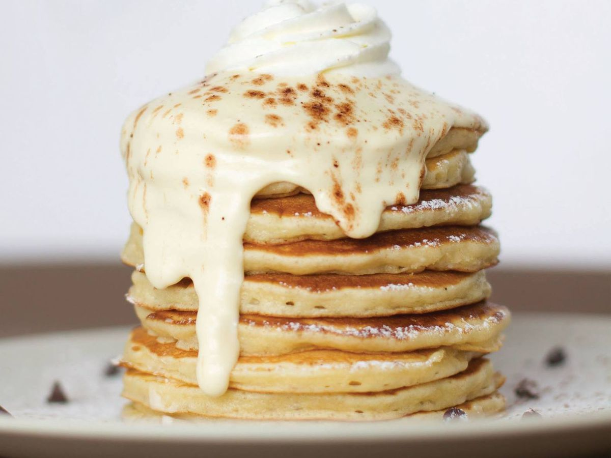 A plate of pale pancakes with cream dripping down from the top.