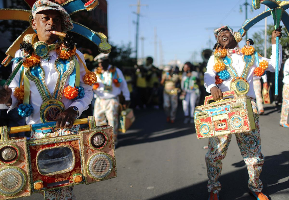 Two costumed men wear garlands and hold colorful prop beaded boom boxes