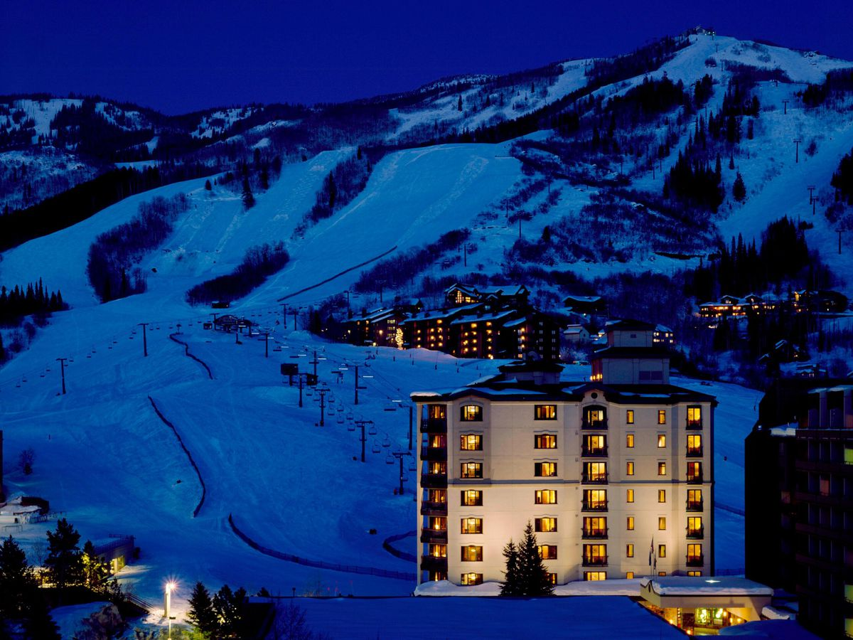 A ski resort at night has white snowy ski slopes and a multi-story hotel in the foreground. Windows glow in the hotel.
