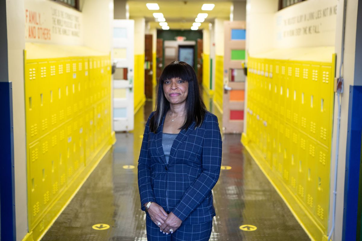 Dr. Dionne Ledford, wearing a blue checkered pantsuit, smiles for a portrait standing in the hallway of Roseville Community Charter School, with rows of yellow lockers on either side of her.