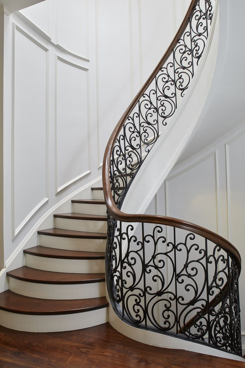 A spiral staircase with cast iron filigree banister.