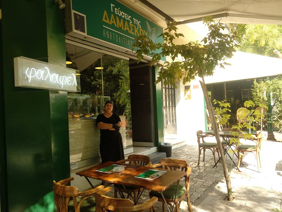 A woman in chef's wear stands outside a glass-fronted cafe with the name above the store and a neon sign nearby, along with outdoor tables beneath an awning on a sunny day