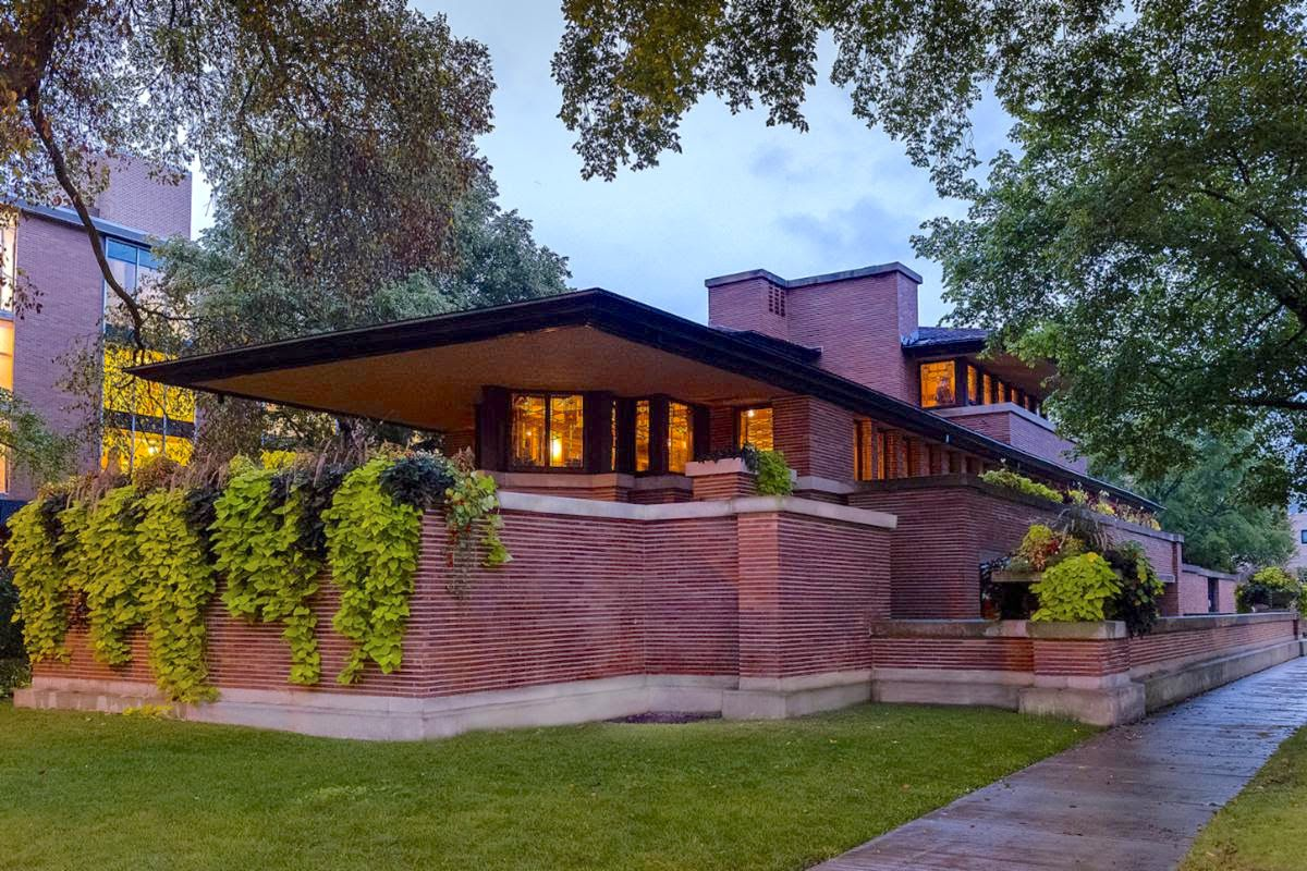 A long structure with brick walls on the lower level topped by a wall of windows and a broad, overhanging roof. The home glows from within at dusk.