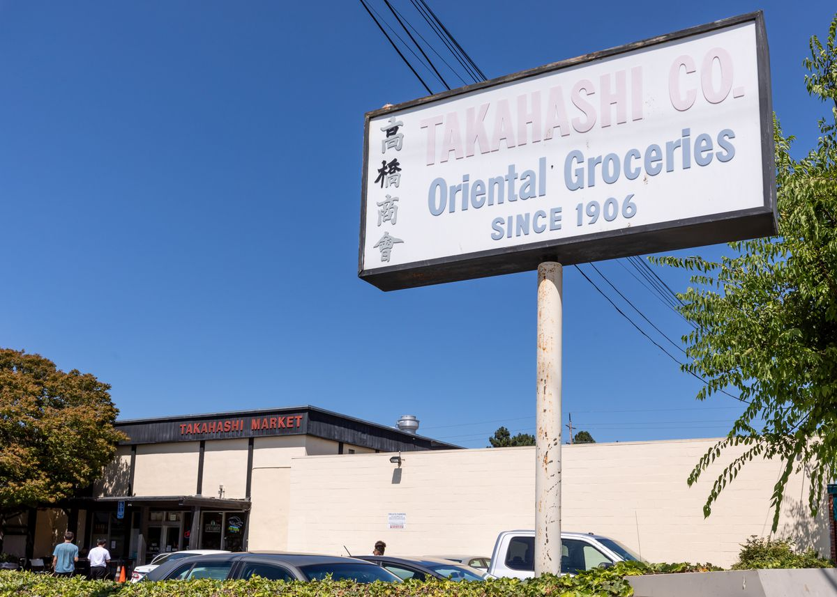 """A sign outside a parking lot that reads """"Takahashi Co. Oriental Groceries Since 1906"""""""