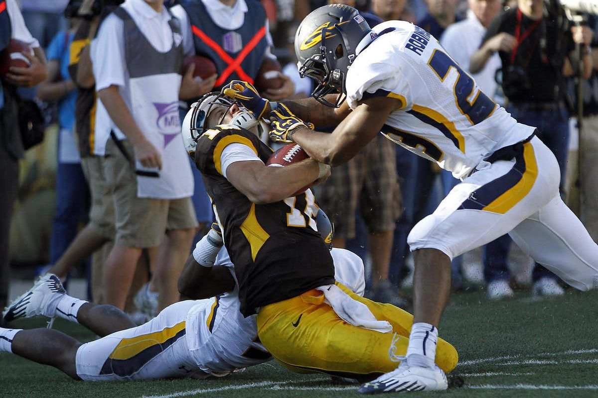 Wyoming quarterback Brett Smith takes a hit from Toledo's Jermaine Robinson during an NCAA college football game in Laramie, Wyo., Saturday, Sept. 8, 2012.