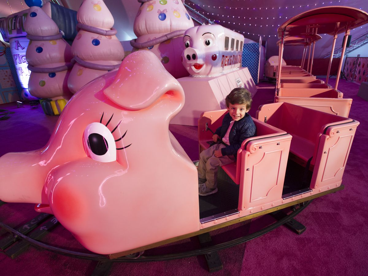 Boy riding pink train that looks like a pig.