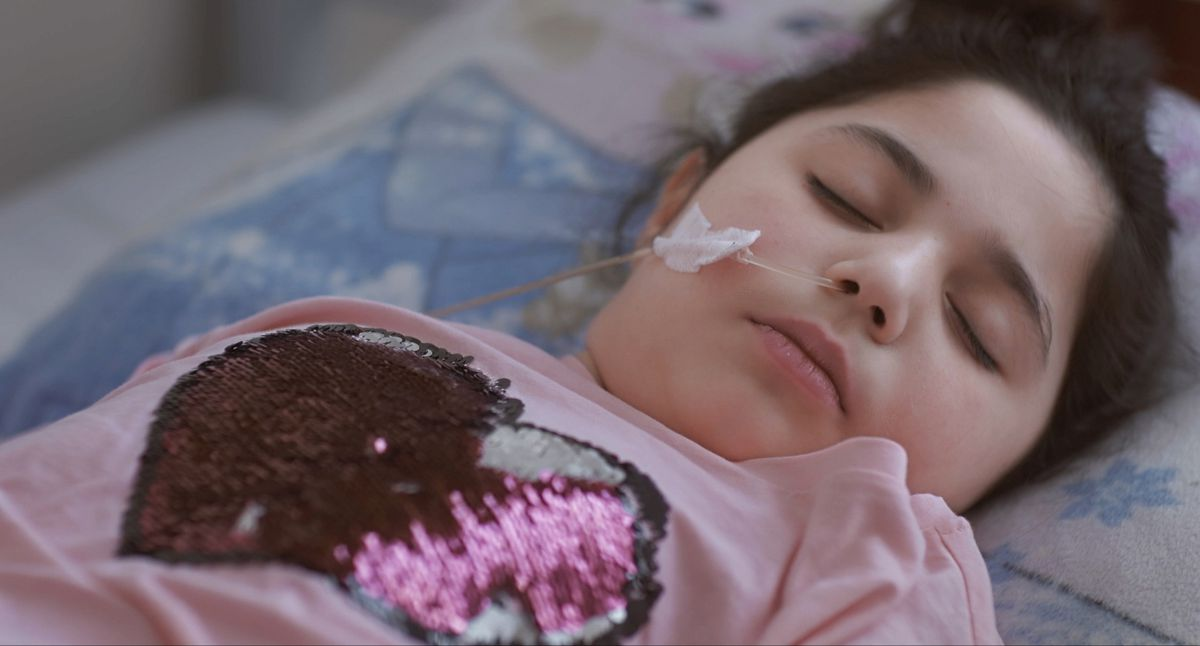 A small child lies in a coma-like state from the documentary Life Overtakes Me