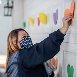 Brandy Greene puts up notes on the Stewart's garage in Clinton on Saturday, Jan. 30, 2021.Friends, family, and neighbors gathered to watch Brandon Stewart go for a ride in BYU football's equipment semi in Clinton on Saturday, Jan. 30, 2021. The ride was his final wish as he battles cancer.