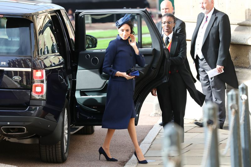 Meghan Markle emerges from a black car.
