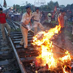 Indian railway policemen try to remove a burning effigy representing the Indian government during a protest along railway tracks in Allahabad, India, Thursday, Sept. 20, 2012.  Angry opposition workers have disrupted train services as part of a daylong strike in India to protest rising diesel prices and the government's decision to open the country's huge retail market to foreign companies.