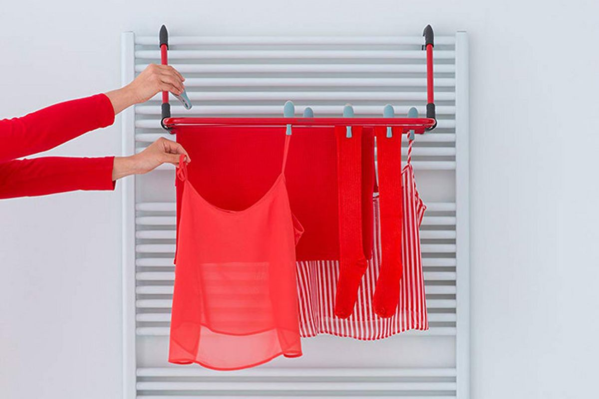 Red garments hang on a red shelf.