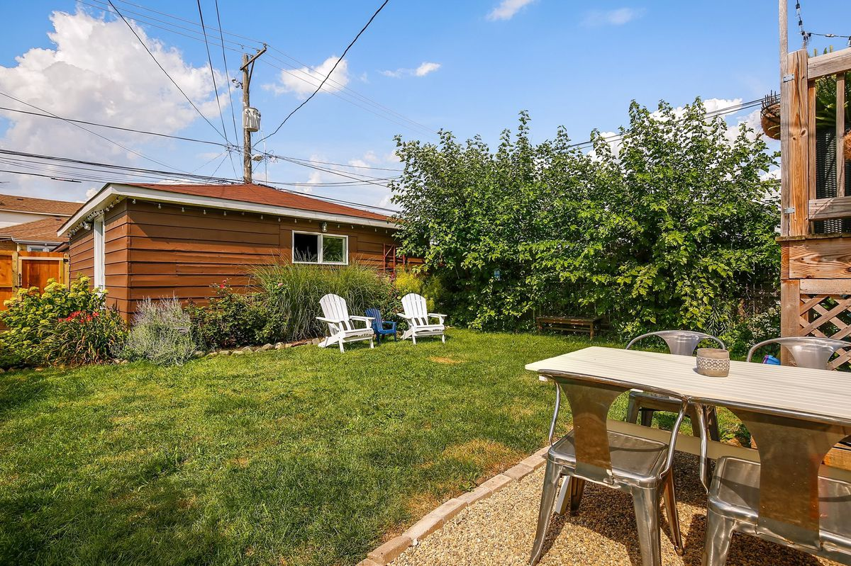 There's a partial view of a four-seat outdoor table that's next to an open, grassy backyard with three Adirondack chairs. There's tall grasses and flowers around the cedar wood garage.