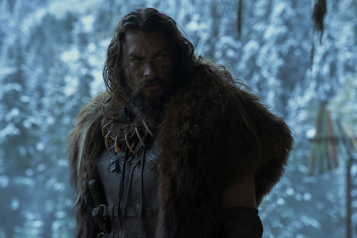 Jason Momoa as Baba Voss shoots a look while wearing layered fur in front of white snowy trees