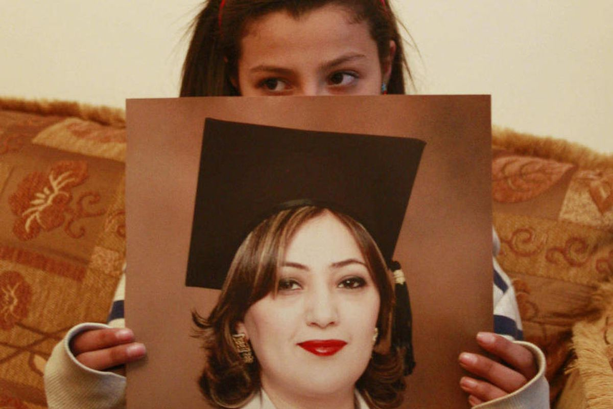 Lilyan, daughter of Palestinian Ismat Abdul-Khaleq, a West Bank university lecturer, holds a photograph of her mother at the family house in in the West Bank city of Ramllah, Monday, April 2, 2012. Abdul Khaleq was arrested by Palestinian security forces