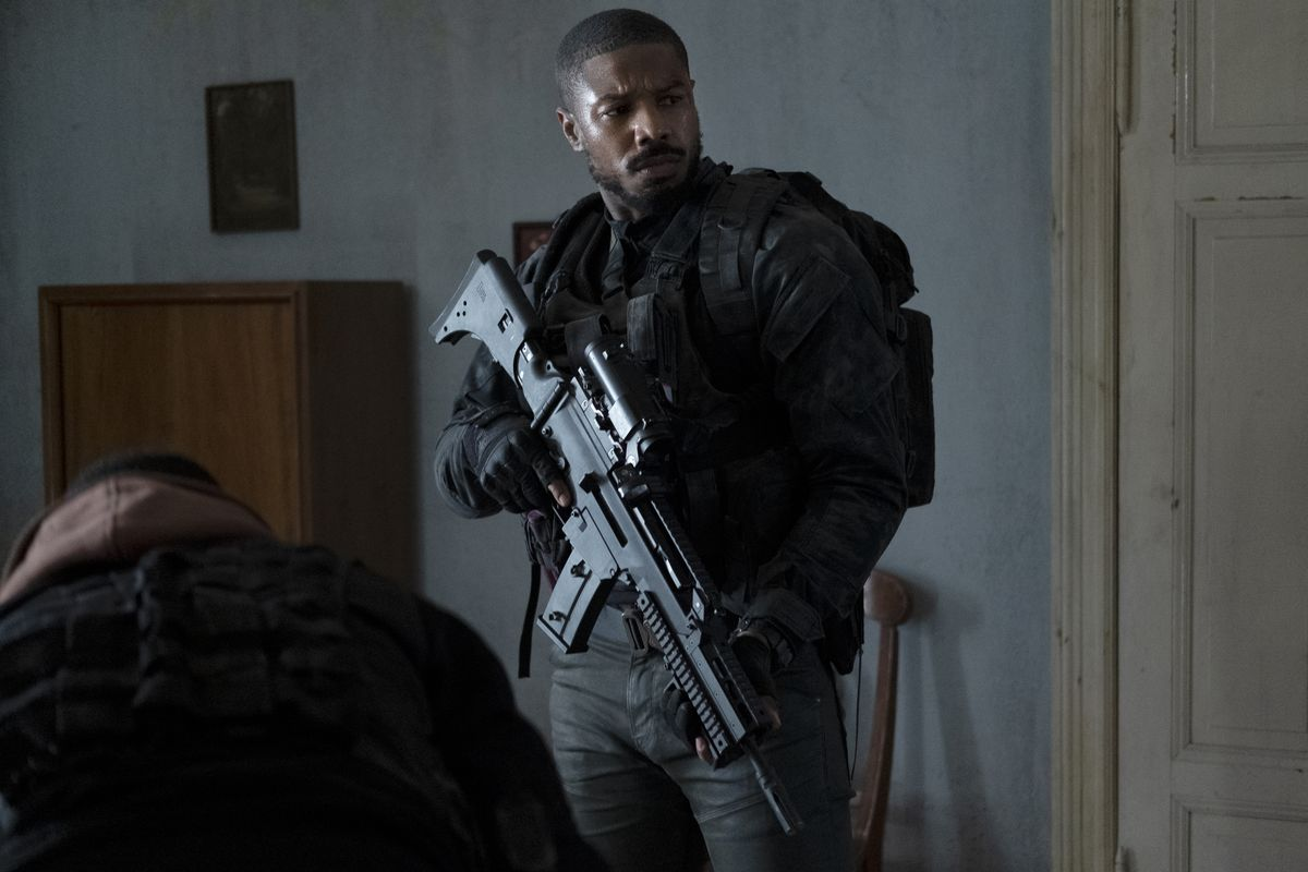 A glowering Michael B. Jordan hefts a very large assault rifle in Tom Clancy's Without Remorse