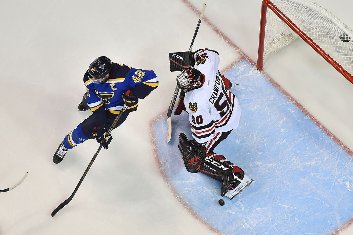 Chicago Blackhawks goalie Corey Crawford (50) makes a save against the attack of St. Louis Blues center David Backes (42)
