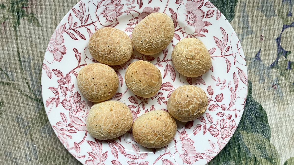 Seven pao de queijo from Brazi Bites sit on a decorative white and magenta plate